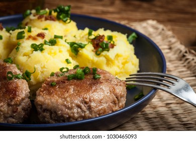 Meatballs served with boiled potatoes on a plate.