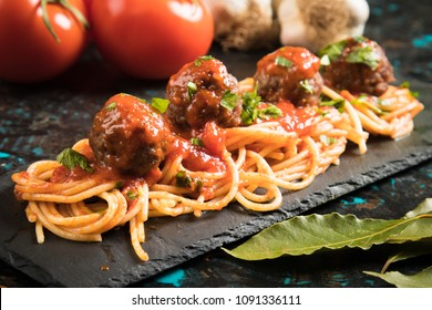 Meatballs served over italian spaghetti pasta with tomato sauce