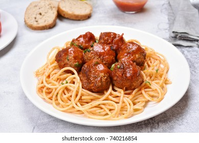 Meatballs and spaghetti on plate, close up view.