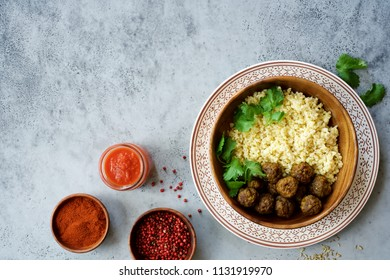 Meatballs with spices and bulgur garnish in wooden bowl. Gray food background
