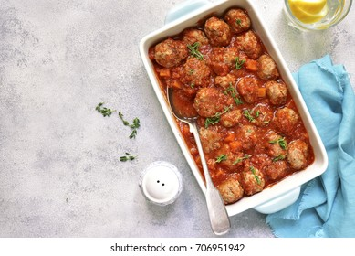 Meatballs stewed with carrot and onion in tomato sauce on a light slate,stone or concrete background.Top view.