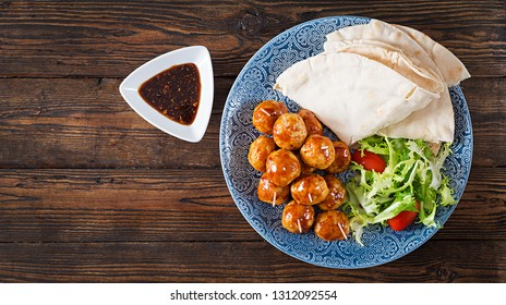 Meatballs in sweet and sour glaze on a plate with pita bread and vegetables in a Moroccan style on a wooden table. Tapas. Trend food. Top view