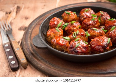 Meatballs in sweet and sour tomato sauce. Homemade roasted beef meatballs in cast-iron skillet.