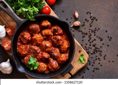 Meatballs in sweet and sour tomato sauce on the kitchen table. Top view