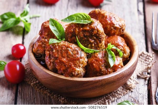Meatballs with tomato sauce and basil, vintage wooden background, selective focus