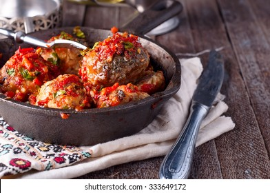 meatballs with tomato sauce in black pan in backgraund