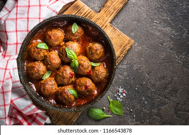 Meatballs in tomato sauce in a frying pan on dark stone table. Top view with copy space.