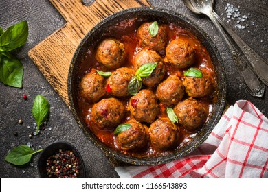 Meatballs in tomato sauce in a frying pan on dark stone table. Top view.