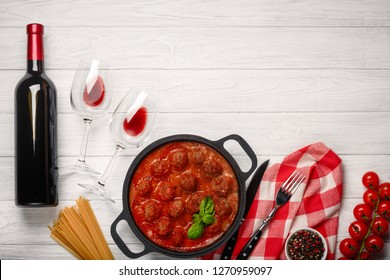 Meatballs in tomato sauce in a frying pan with cherry, tomatoes, bottle of wine and two glasses on a white wooden board. Top view.