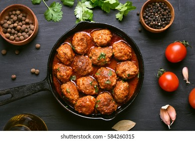 Meatballs with tomato sauce and green herbs in frying pan on black background, top view