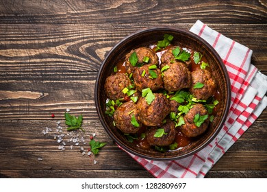 Meatballs in tomato sauce and greens on dark wooden table. Rustic style. Top view with copy space.
