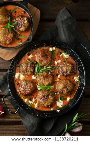 Meatballs with tomato sauce on black skillet
