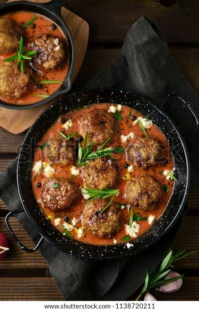 Meatballs with tomato sauce on black skillet