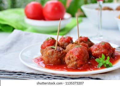Meatballs in tomato sauce on white plate with Greek basil herb