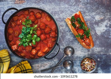 Meatballs with tomato sauce in pot and delightful sub sandwich beside. Top view, blank space