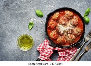 Meatballs in tomato sauce in a skillet pan over dark grey slate,stone or condrete background.Top view.