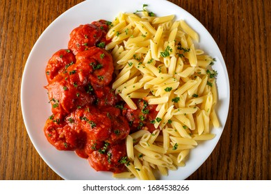 Meatballs in tomato sauce with small penne pasta - top view