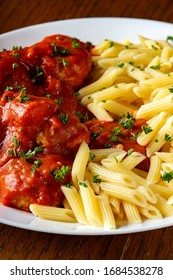 Meatballs in tomato sauce with small penne pasta on plate