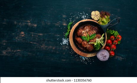 Meatballs with tomato sauce and vegetables in a frying pan. On a wooden table. Top view. Copy space.
