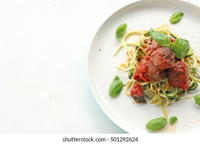 Meatballs in tomato sauce with zucchini and basil