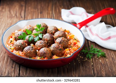 Meatballs with vegetable sauce in cast iron skillet on wooden background, selective focus