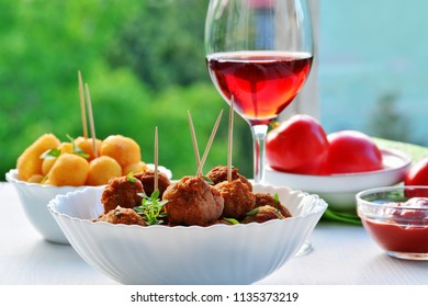 Meatballs in white bowl , glass of red wine cheese balls and tomatoes on white wooden table outdoors.