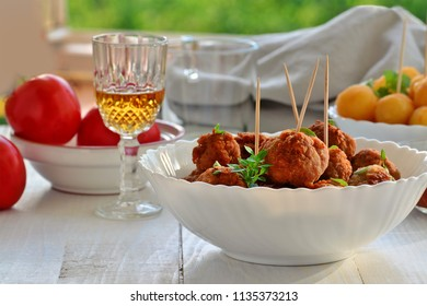 Meatballs in white bowl with a glass of whiskey, other snacks and food ingredients on the table. Shallow dof.