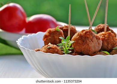 Meatballs in white bowl on an outdoor table, tomatoes in the background, closeup