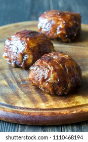 Meatballs wrapped in bacon on the wooden board