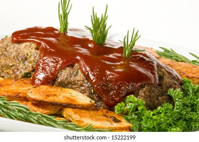 Meatloaf with fresh herbs, tomato sauce, and pan fried potatoes on white serving platter.