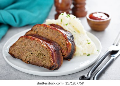Meatloaf wrapped in bacon with mashed potatoes