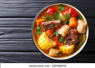 Sancochois a meats and vegetables stew, enjoyed in Latin America and the Spanish Caribbean islands close-up on a bowl on the table. Horizontal top view from above