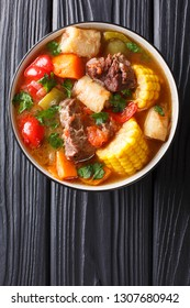 Sancochois a meats and vegetables stew, enjoyed in Latin America and the Spanish Caribbean islands close-up on a bowl on the table. Vertical top view from above