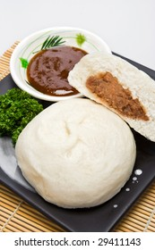 "Meat-stuffed bread a.k.a. ""Siopao"" with hoisin sauce on the side."