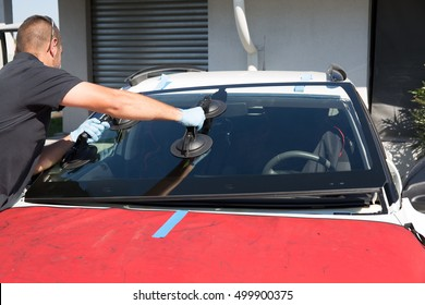 Mecanic man is changing windscreen on a car