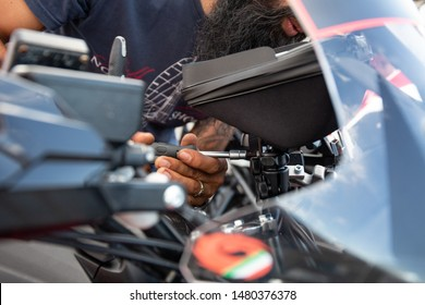 Mecanic working with a screwdriver on a motorcycle