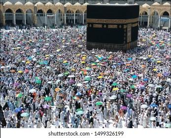 MECCA, SAUDI ARABIA- AUGUST 26, 2019 : Hajj pilgrims shade themselves from blistering heat with colorful umbrella during hajj season in Makkah, Saudi Arabia.