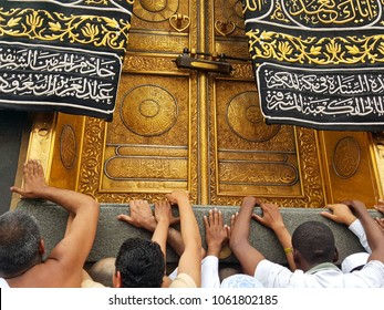Mecca / Saudi Arabia - December 14 2015 : Pilgrims holding the step in front of Kaabah's golden door called Multazam, while praying and asking for God's forgiveness.