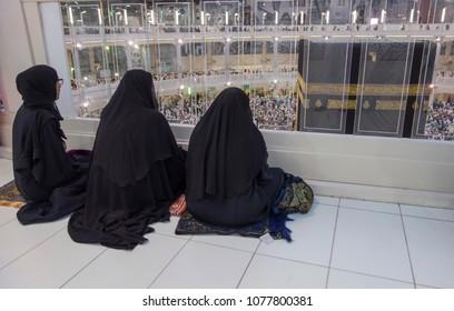 MECCA, SAUDI ARABIA - DECEMBER 23, 2014 : Three unidentified Muslim women watch the Kaabah in Makkah, Saudi Arabia.