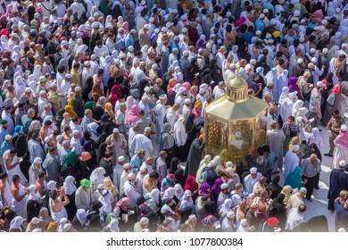 MECCA, SAUDI ARABIA - DECEMBER 24, 2014 : Muslim pilgrims walk pass by a Abraham sacred place (maqam Ibrahim) and circumambulate the Kaabah in Makkah, Saudi Arabia.