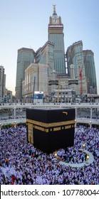 MECCA, SAUDI ARABIA - DECEMBER 24, 2014 : Muslim pilgrims circumambulate and touch the Kaabah cloth (kiswah or kiswa) in Makkah, Saudi Arabia. Zamzam tower in the background.
