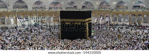 MECCA, SAUDI ARABIA - DECEMBER 5, 2016: Muslim performing tawaf at holy Kaabah in the afternoon. Muslims face the direction of Kaaba when performing prayer