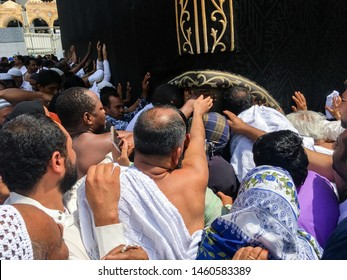 MECCA, SAUDI ARABIA - JUNE 28: Unidentified Muslim pilgrims in white ihram touch black cloth of Kaaba with Allah and Muhammad (peace be upon him) inscriptions on June 28, 2019 in Mecca Saudi Arabia.