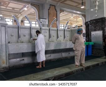 MECCA, SAUDI ARABIA - JUNE 4, 2019 :  Worker looks on while a Muslim pilgrim in ihram white clothes drink zamzam water inside  Haram Mosque in Mecca, Saudi Arabia.