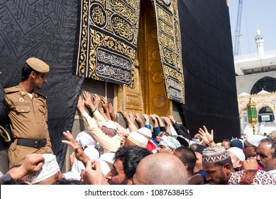 MECCA, SAUDI ARABIA - MAY 01 2018: Crowd of people touching the Holy Kaaba in Masjid Al Haram in Makkah. Doors and arabic text covered with gold. Entrance to the Kaaba is closed with massive lock