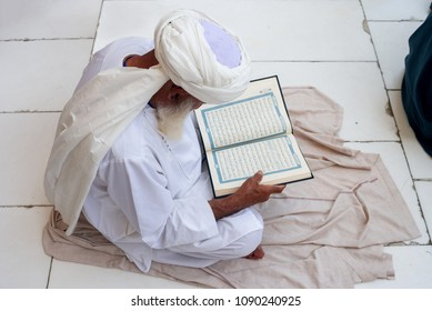 MECCA, SAUDI ARABIA - MAY 02 2018: Old man sitting in Masjid Al Haram near Holy Kaaba, reading Quran before Prayer Time
