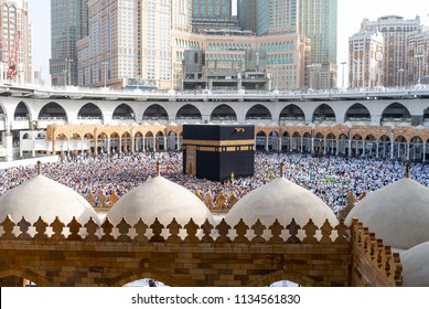 MECCA, SAUDI ARABIA - MAY 02 2018: View on Holy Kaaba from second or third floor of Masjid Al Haram. People walking 7 times around Kaaba making Tawaf, Skyscrapers on background, Abraj Clock Tower