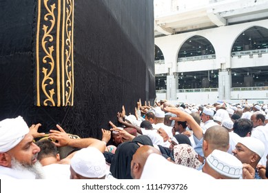 MECCA, SAUDI ARABIA - MAY 03 2018: People walking around Holy Kaaba in Masjid Al Haram Mosque in Mecca. Touching Kaaba silk cover Kiswah and praying. Crowd of people always around Black Stone