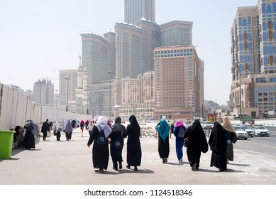MECCA, SAUDI ARABIA - MAY 07 2018: People walking toward Masjid Al Haram Holy Mosque in Mecca for daily prayer. The buildings are luxury hotels in the center. People wear classic Arabic islamic dress.
