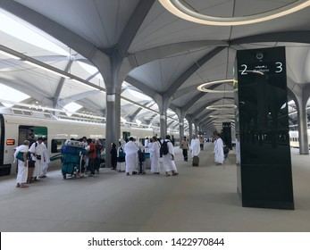 MECCA, SAUDI ARABIA - MAY 27, 2019 :  a group of men in white ihram clothes disembark from train coaches at HSR Mecca station in Mecca, Saudi Arabia.